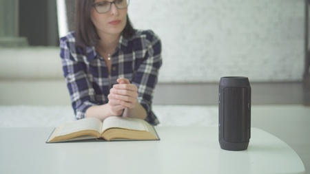 portrait beautiful woman in glasses uses voice assistant while reading a book