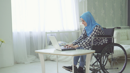 girl in hijab disabled person on a wheelchair using a laptop