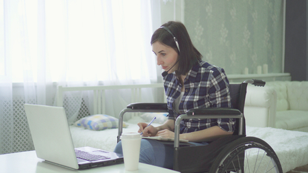 young woman disabled, wheelchair, remote work at home, computer headset Stockfoto