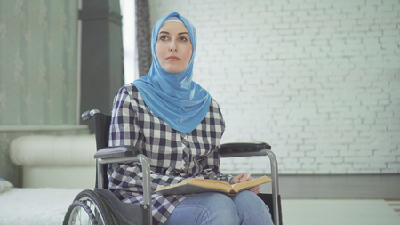 A beautiful young woman in a hijab is blind or weakly imposing, a wheelchair reading a braille font. Stockfoto