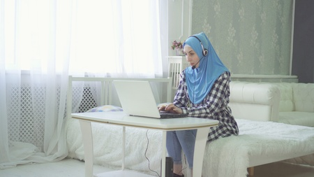 beautiful woman in hijab at the computer at home with a headset, remote work on 版權商用圖片
