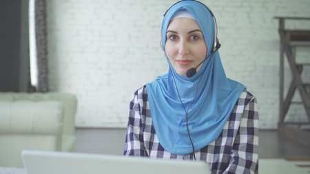 young beautiful woman in hijab with headphones and headset, call center worker Stockfoto