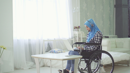 beautiful young woman in hijab disabled person smiling, wheelchair, teleworking in the Internet