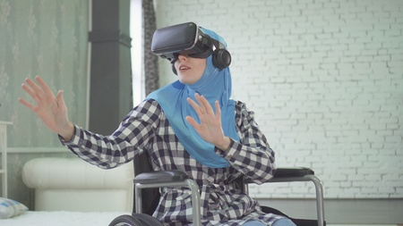woman in hijab, wheelchair, uses VR glasses, 3D technology