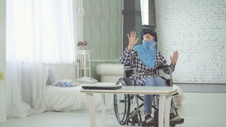 woman in hijab , wheelchair, uses VR glasses, 3D technology, virtual travel