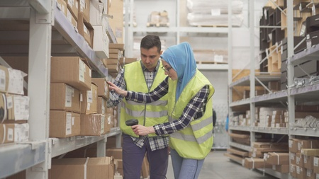 Man store worker shows a muslim woman how to use a barcode scanner Stockfoto