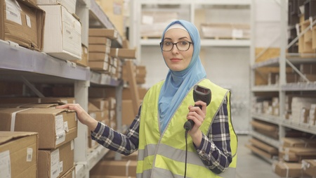Portrait muslim in hijab shop worker with barcode scanner