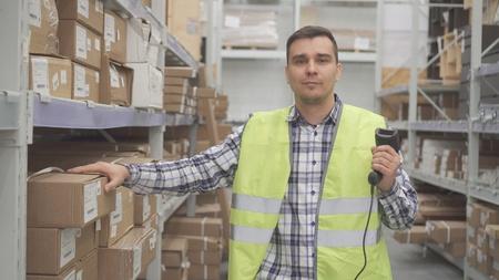 Portrait man store worker using bar code scanner scanning labels on boxes