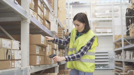 Store worker in the warehouse using a barcode scanner conducts accounting Stockfoto