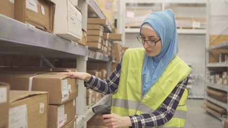 Muslim in hijab store worker conducts accounting using barcode scanner