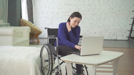 portrait of a smiling young beautiful disabled woman in a wheelchair, working at home on a laptop, remote work on the Internet 版權商用圖片