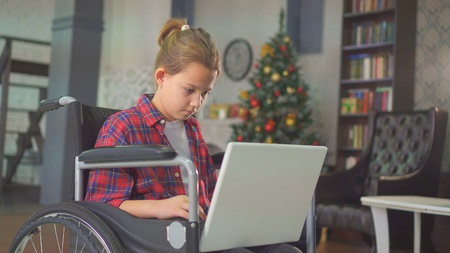 teenage girl disabled in a wheelchair, sitting at the laptop, against the Christmas tree