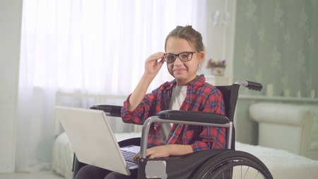 teenage disabled girl in a wheelchair using a laptop and looking at the camera smiling Stockfoto