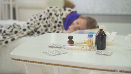 little girl is sick with a cold at home, there are pills and medicines in the background