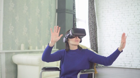 young beautiful disabled woman in a wheelchair at home, uses 3d technology, vr helmet