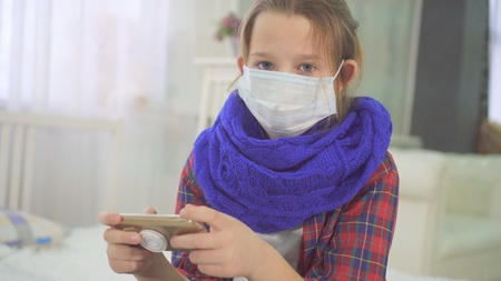 portrait of teen girl with medical mask looking at camera sitting at home on bed