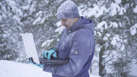 Portrait frozen man in winter forest uses laptop