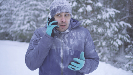 Frozen man in the winter forest talking on the phone 版權商用圖片