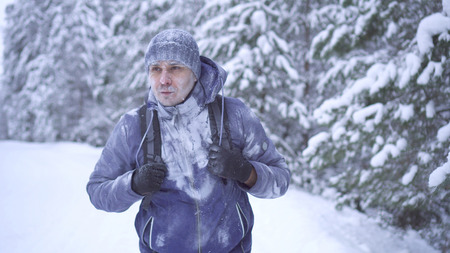 Portrait frozen man with a backpack, covered with snow in the winter forest.