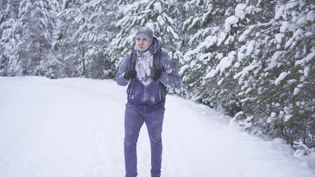 Frozen man with a backpack, covered with snow in the winter forest. Stockfoto