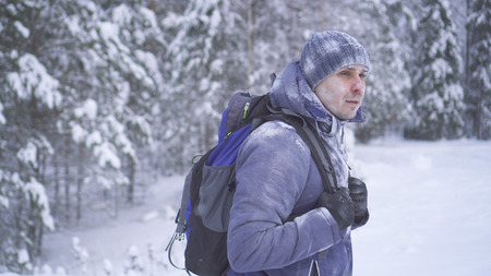 Portrait frozen man covered with snow in the winter forest