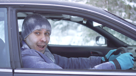 Joyful frozen man sitting in the car and looking at the camera