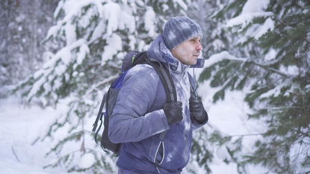 Frozen man covered with snow in the winter forest