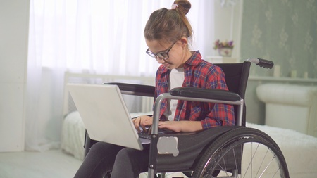 portrait of a teenage disabled girl in a wheelchair using a laptop