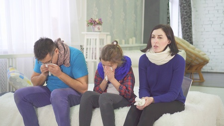 the family has a cold, mom dad and daughter sneeze sitting at home on the bed