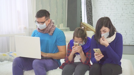 the concept of the epidemic, the family is sick and coughing, sitting at home, in medical masks