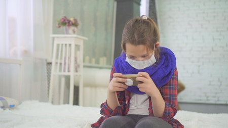 teenage girl with a medical mask.sitting at home on the bed
