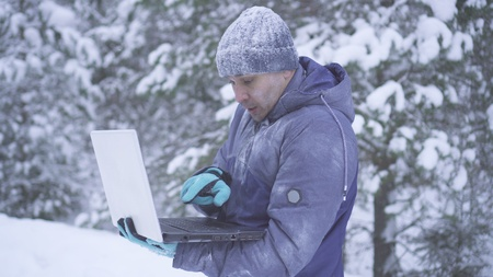 Frozen man in winter forest uses laptop