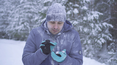 Frozen man in the winter forest uses the phone