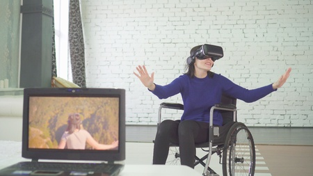 portrait of disabled woman in a wheelchair atechnology, vr helmet, virtual travel