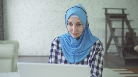 young beautiful woman in hijab with headphones and headset, cal center worker