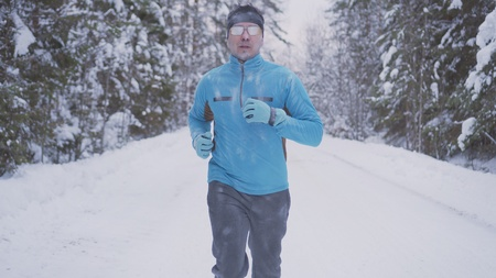 portrait of a man 30 years old, running through the winter forest