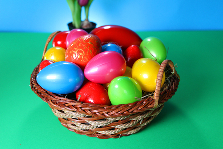 Easter eggs on basket. Colorful plastic decorations.