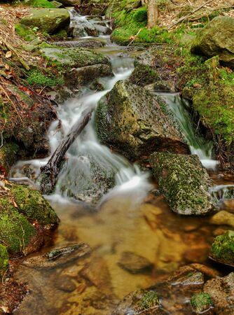 Waterfall on mountain stream photo