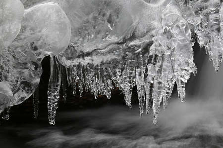 frozen creek: Icicles on a frozen creek Stock Photo