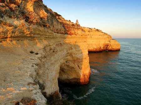 Algarve Portugal. Wild yellow rock cliffs and green-blue ocean. Stock Photo