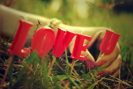 truelove: An in love girl placing on the grass the letters that form the greatest phrase in the world  I love u  Stock Photo