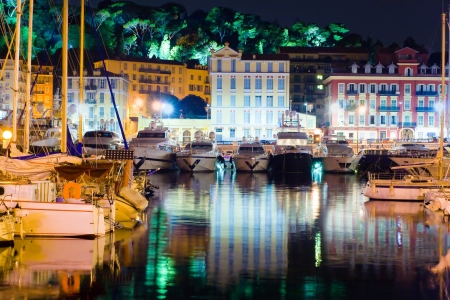 Image of yacht parked with a beautiful reflection of the city at night. In the background are seen the lights of the park in Nice, France photo
