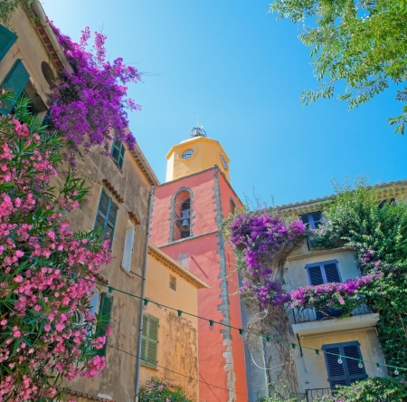 balcony window: The image of the clock tower with facades of adjacent buildings in beautiful flowers against the blue sky, San Tropez. Stock Photo