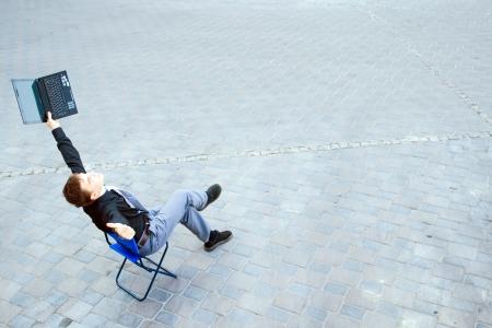 Das Bild auf einem Geschäftsmann sitzt auf der Straße, Arbeiten, die mit dem Computer und hat einen Erfolg. Standard-Bild - 15036293