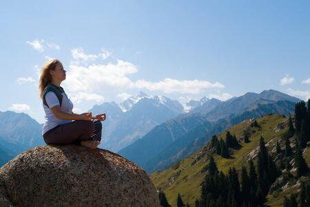 Yoga at summit with aerial view of the mountain range photo