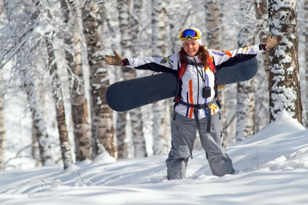 freeride: Portrait image of young snowboarder women is going for freeride to uphill through forest