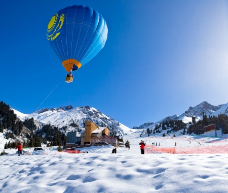 Balloon flying above mountain range at clear blue sky. Winter ski resort of Chimbulak, Almaty, Kazakhstan