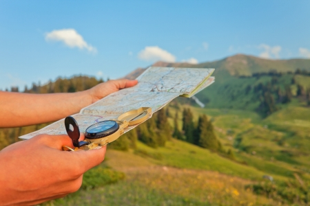 Afbeelding van de hand van de toerist met de kaart met behulp van een kompas. Op de achtergrond een prachtige vallei met de toppen van de bergen bij zonsondergang. Zwitserland.