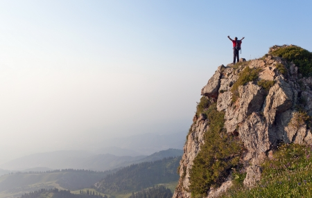 free climber: Image of mountain scenery, on top of which stands the silhouette of a tourist with his hands up, who enjoys success achieved heavy climbing. Stock Photo
