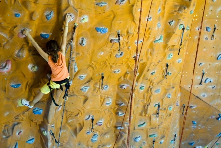 Sport image of climbing teenager (little girls) to the top of wall
